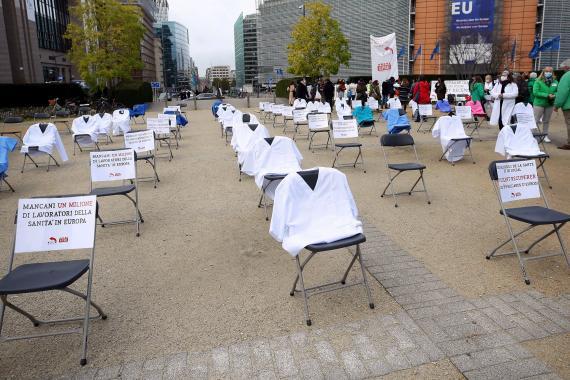 Brüksel'de sağlık çalışanlarını temsilen beyaz önlüklü boş sandalyelerle protesto