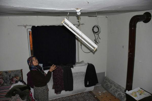 Bir kadın, evinde sarkmış olan floresanı gösteriyor.
