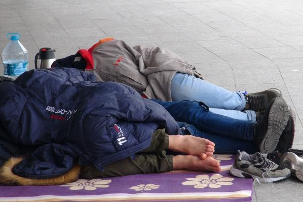 Yerde, betonda incecik battaniyenin üstünde yatan mülteci çocuklar.