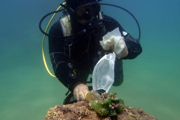 Denizde maske atığını gösteren dalgıç