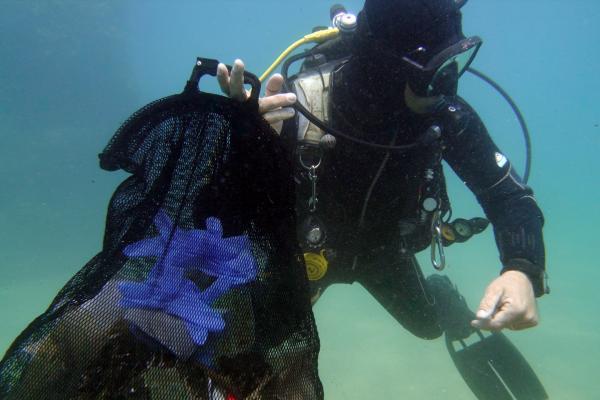 Denizde maske ve eldiven atığını gösteren dalgıçlar