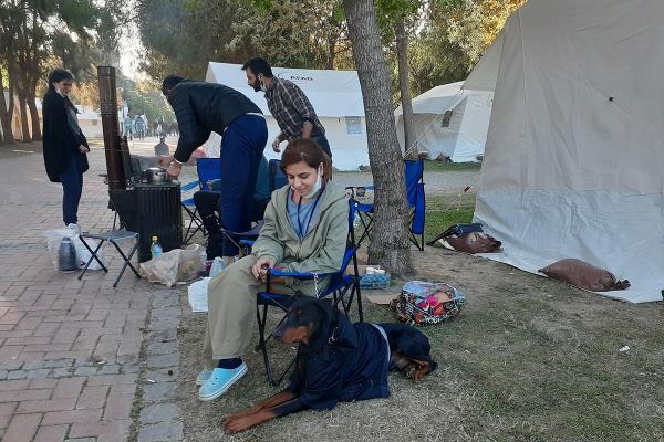 Çadırların yanında köpeğiyle oturan depremzede öğrenci