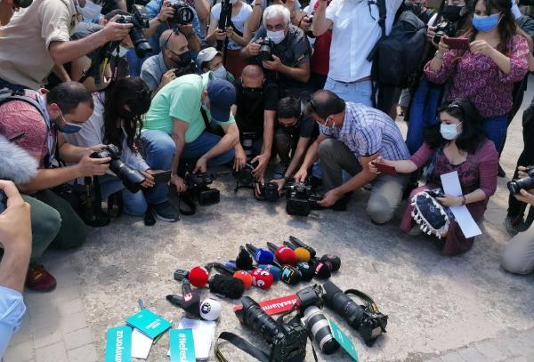 Ankara'da kamera, fotoğraf makinesi ve mikrofonlarını yere koyan gazeteciler