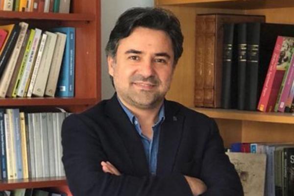 Dr Ali Zafer Sağıroğlu kitaplığın önünde duruyor
