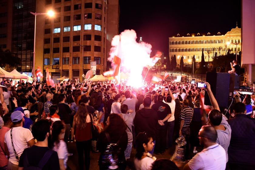 Lübnan'ın başkenti Beyrut'un merkezinde toplanan kalabalık meşaleler yakmış, slogan atıyor.