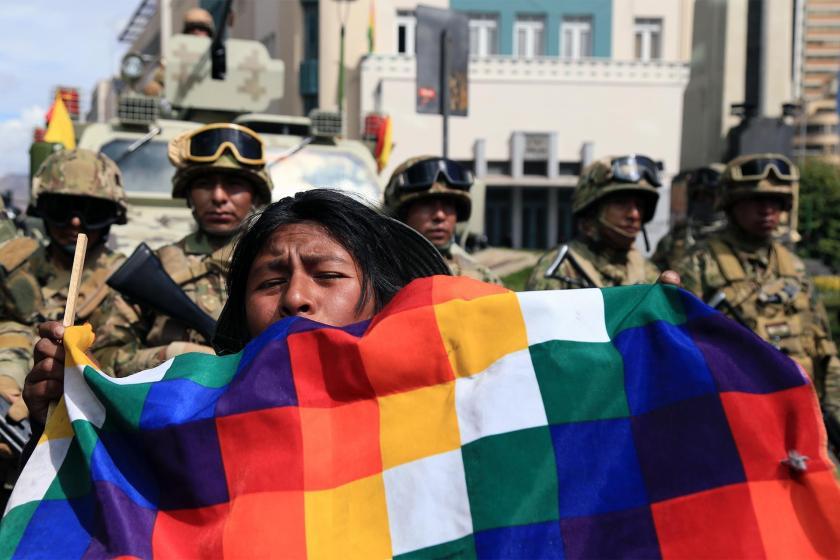 Bolivya'da askeri barikatı önünde darbeyi protesto eden yerli bir kadın ve elinde taşıdığı Whipala bayrağı