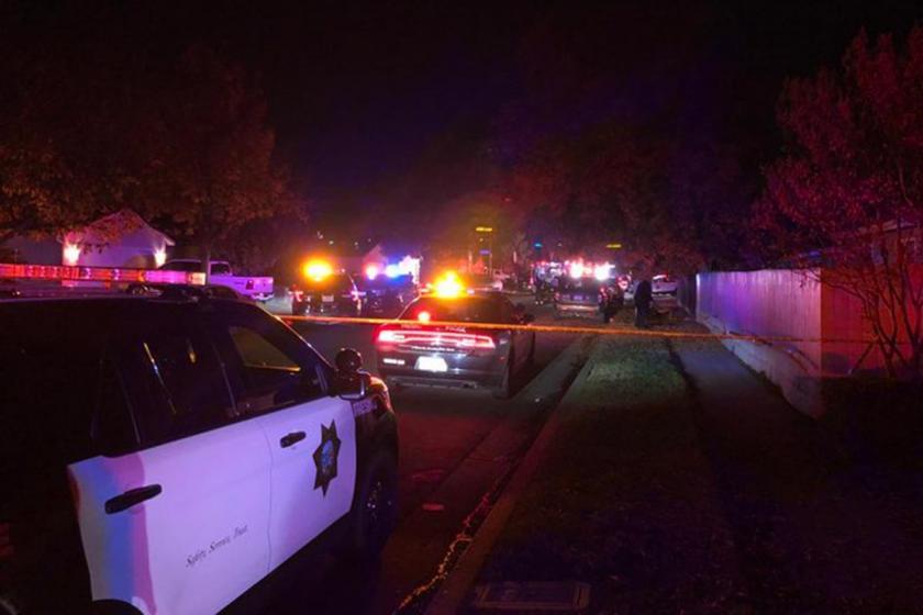 Emniyet şeridi çekilmiş karanlık bir sokak ve çok sayıda polis aracı.