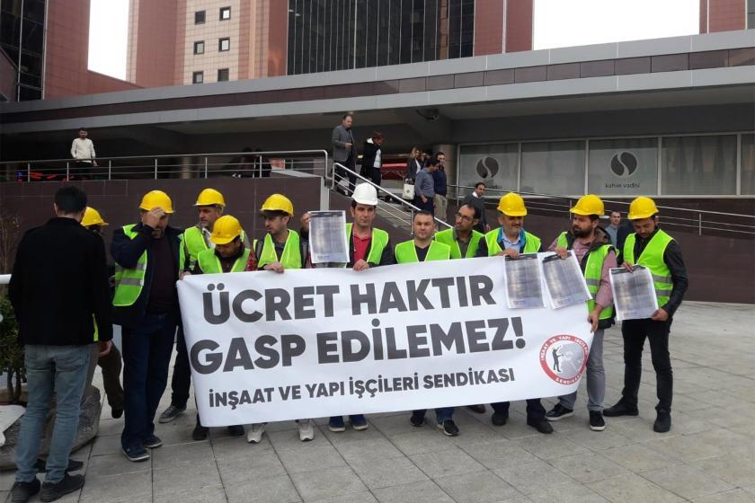 Ödenmeyen ücretleri için  eylem yapan inşaat işçileri basın açıklaması yaparken