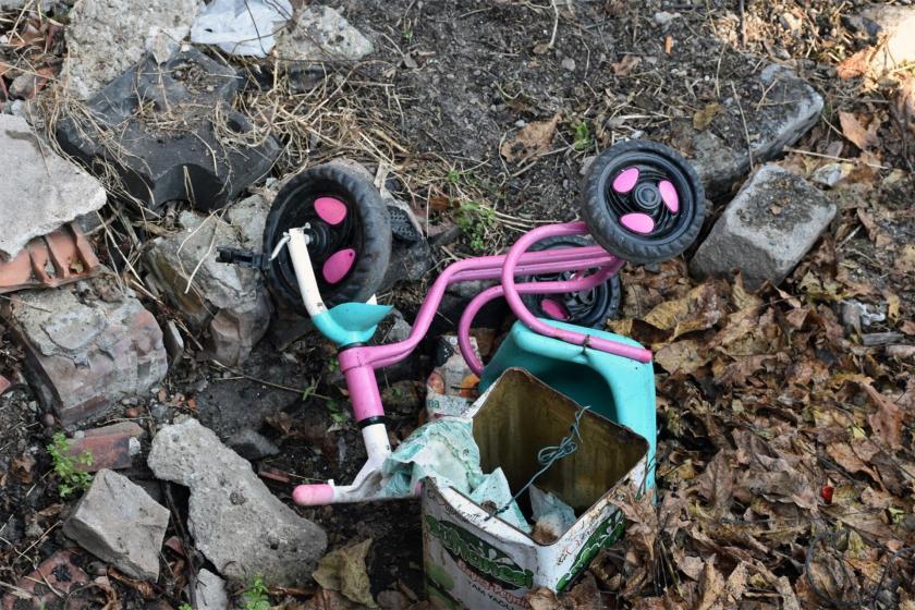 Yanan evin bahçesinde devrilmiş pembe renkli çocuk bisikleti