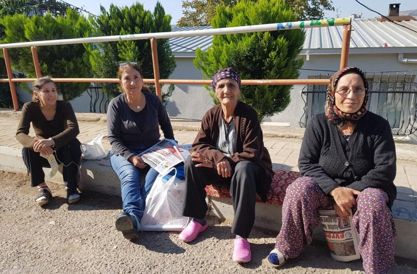 Haberde görüşleri yer alan dört kadın, kaldırımda oturmuş.