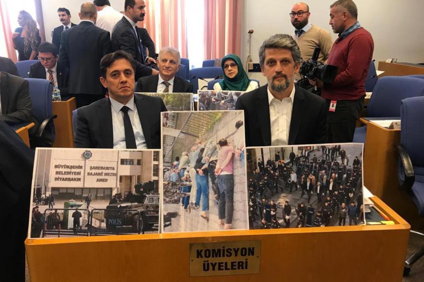Komisyon üyeleri yazan sıralarda oturan HDP'li milletvekilleri ellerinde opeasyonlara dair büyük fotoğraflar tutuyor.