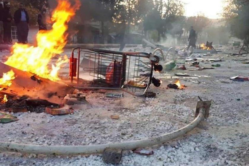 İran'daki protesto gösterileri sırasında sokaktan çekilmiş bir fotoğraf (Yolun ortasında devrilmiş bir alışveriş arabası ve yanan bir ateş)