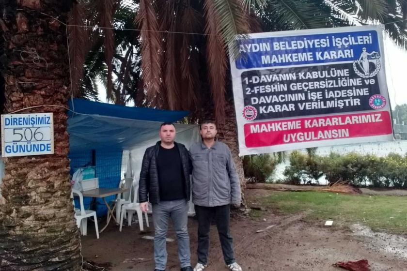 2 Aydın Belediyesi işçisi direniş çadırının önünde poz veriyor