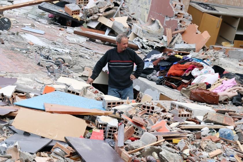 Deprem sonrası yıkılan bir bina enkazın ortasında çaresizlikle çevreye bakan bir depremzede