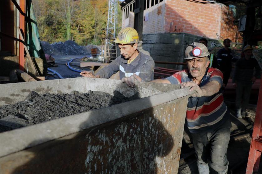 Yer üstünde kömür kovasını iten maden işçileri