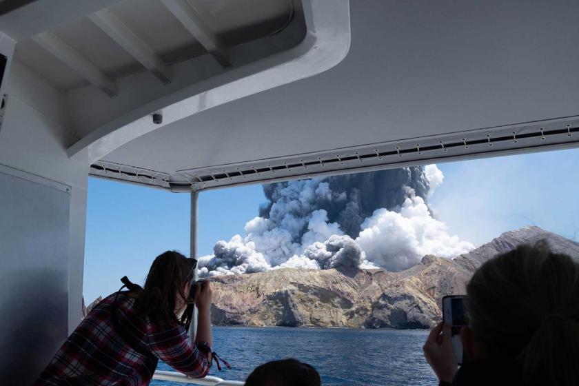 Beyaz Ada'nın yakınındaki bir gemiden fotoğraf çeken gazeteciler ile adanan yükselen dumanlar aynı karede.