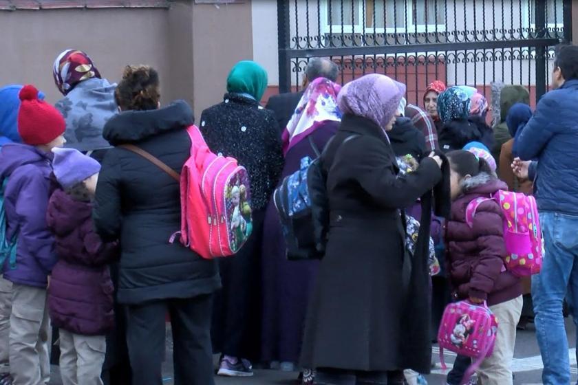 Okul kapısı önünde bekleyen öğrenciler ve veliler