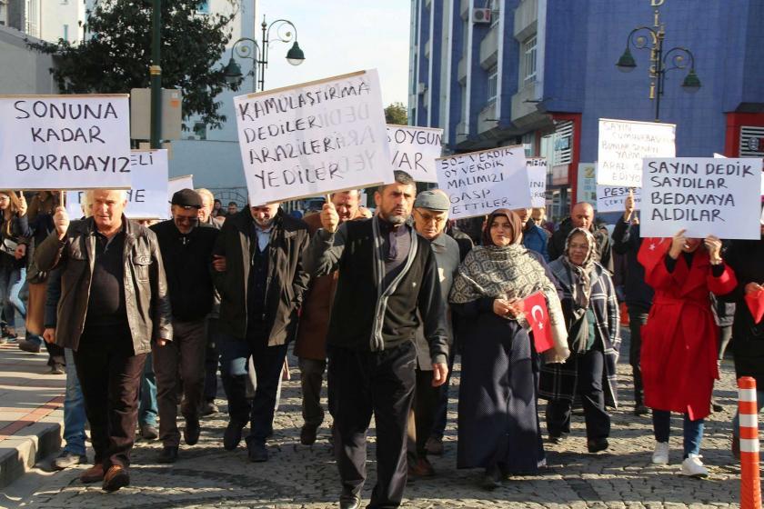 Vatandaşlar ellerinde dövizlerle kamulaştırma bedellerini protesto ediyor.