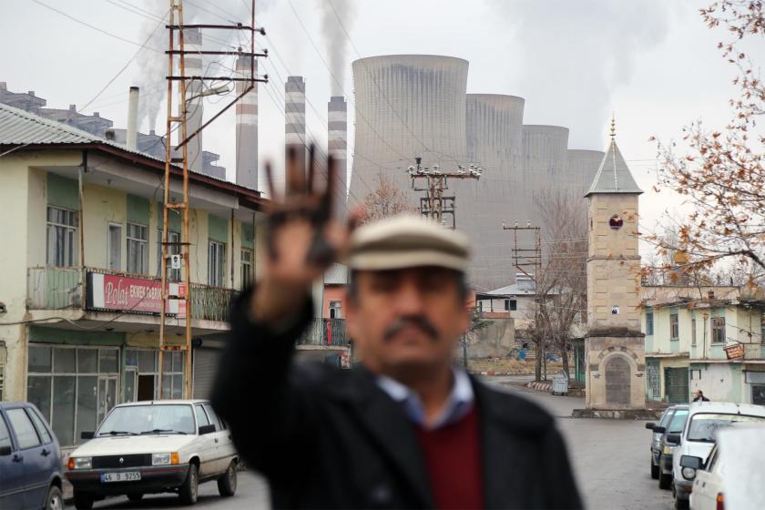 Elindeki siyah isi gösteren bir mahalleli ve arkasında kalan termik santral bacası
