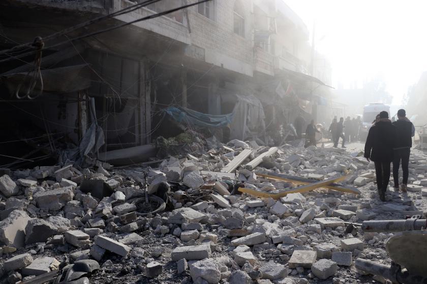 İdlib'de yıkıntılar arasında yürüyen insanlar.