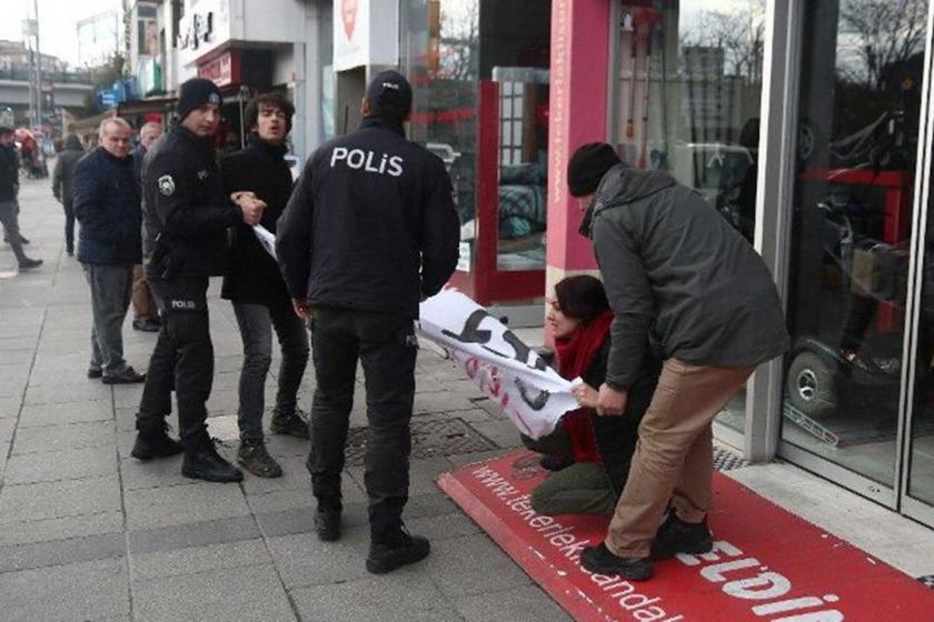 Elinde pankart olan bir kadın gözaltına alınıyor.