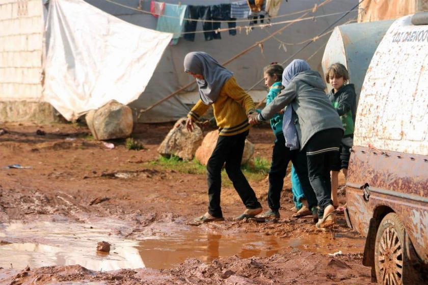 Çamurdan kaçınarak yürümeye çalışan mülteci çocuklar