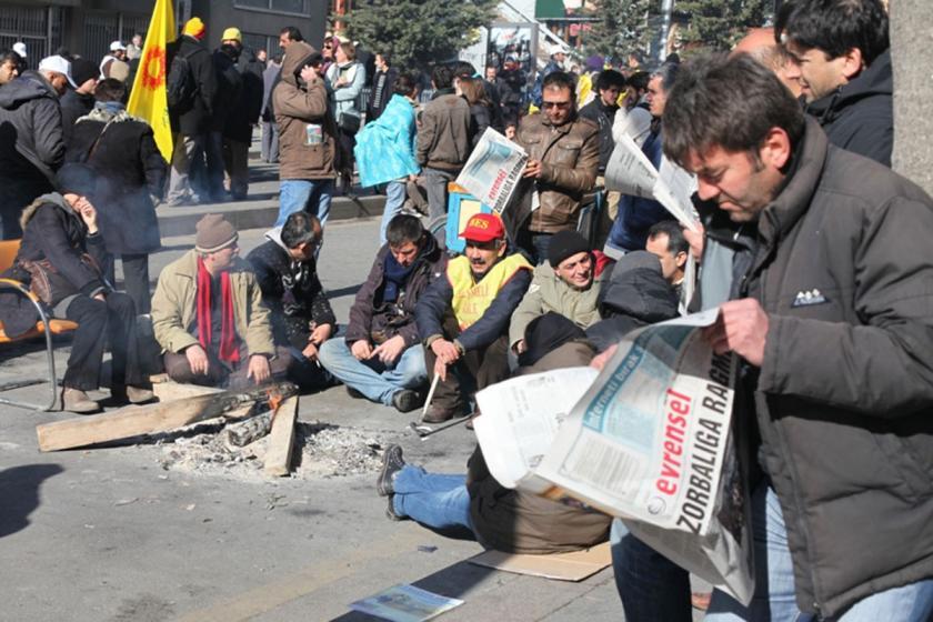 Bir işçi-emekçi eyleminde ateş başında oturmuş emekçilerin bazıları Evrensel okuyor.