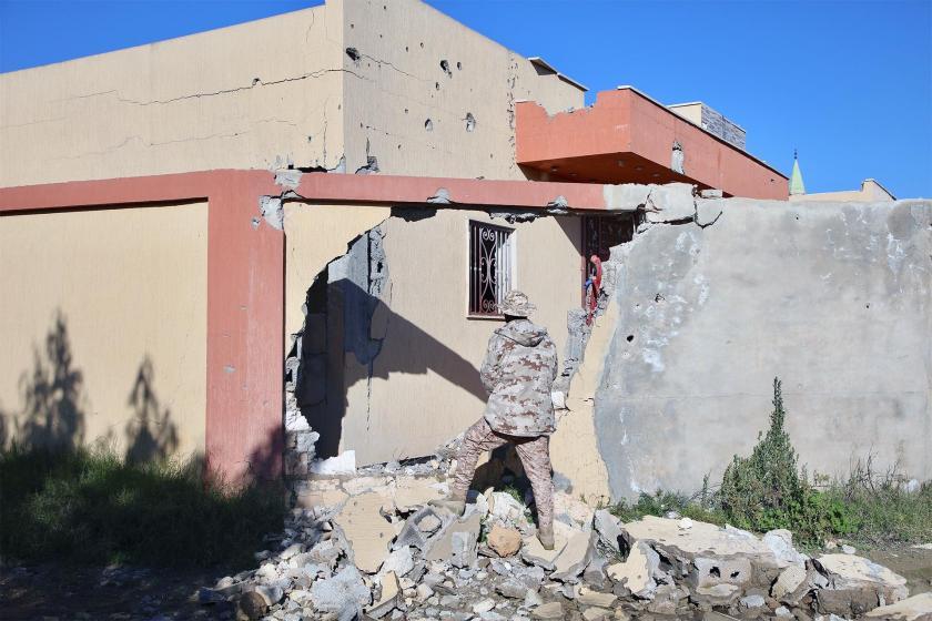 Libya'da iç savaş nedeniyle duvarı yıkılmış bir bina ve bir asker