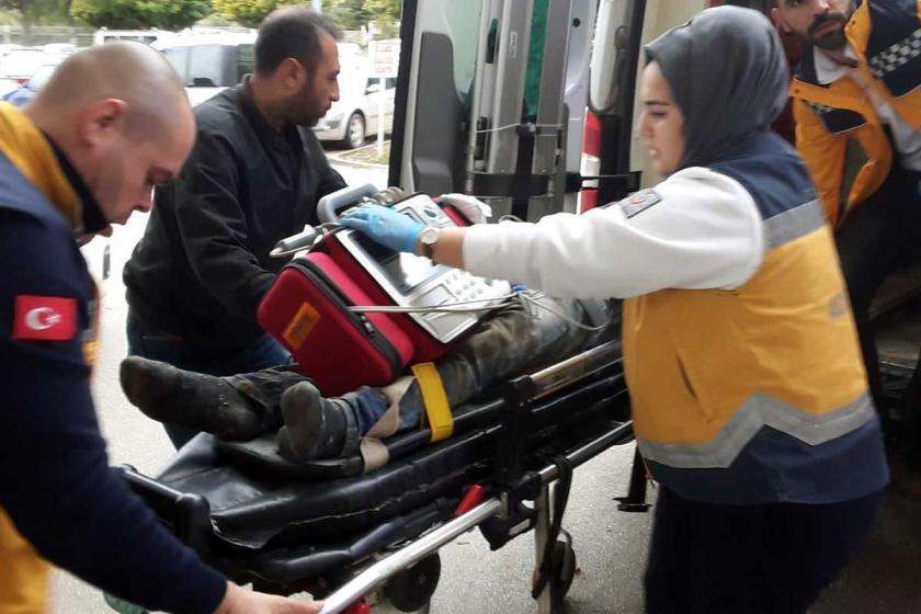 Yaralı işçilerden biri ambulansa taşınıyor.