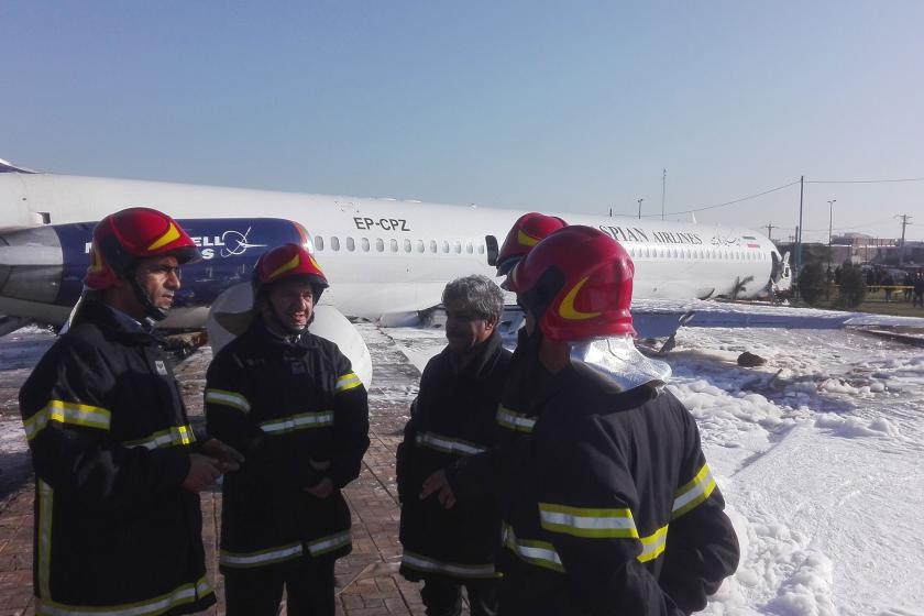 Pistten çıkan yolcu uçağı ve görevliler
