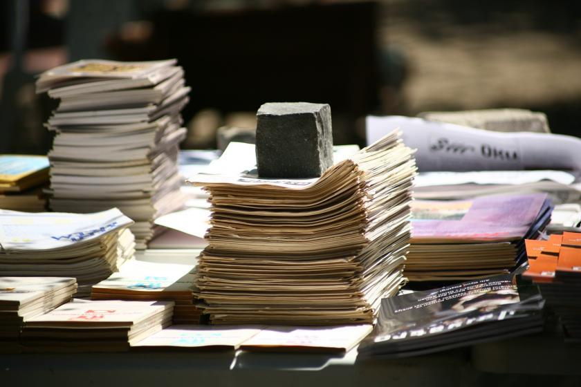 Gazete kağıtları üzerinde ağır bir taş. Bilgi ağırlıktır.