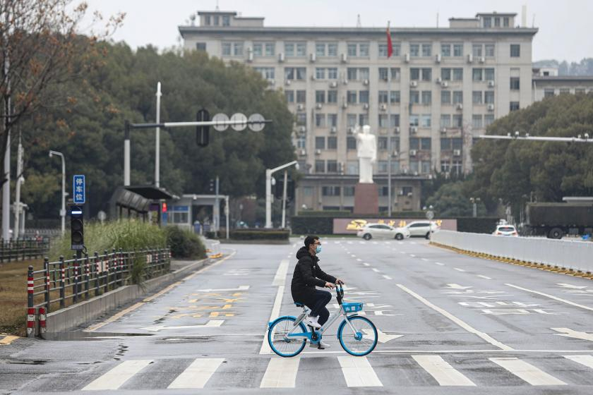 Vuhan'da maske takarak bisiklete binen bir Çinli