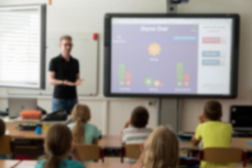 Sınıfta öğrencilerle ders işleyen öğretmen fotoğrafı.