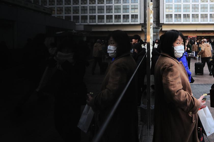 Maske takmış Çinli bir kadın
