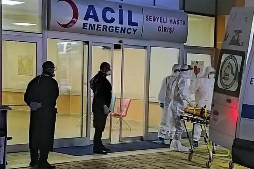 Koruyucu elbiselerle ambulanstan sedye ile hasta indiren sağlık görevlileri