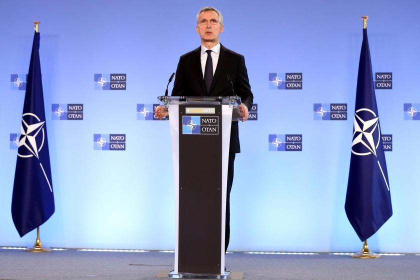 Jens Stoltenberg, iki NATO bayrağı arasında, kürsüden açıklama yapıyor.