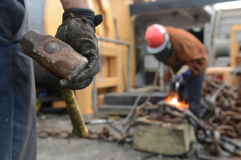 Elinde çekiç olan bir işçi (solda) ve kaynak yapan bir işçi