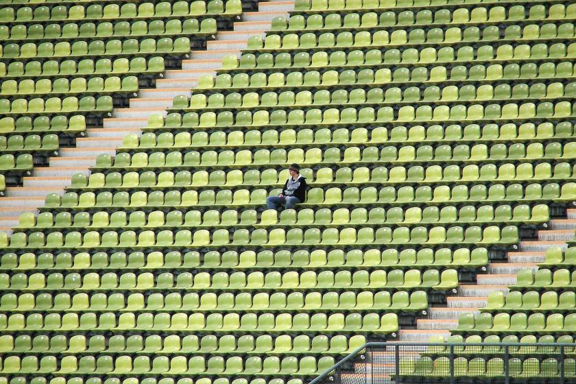 Stadyumda boş tribünde tek başına oturan bir taraftar.