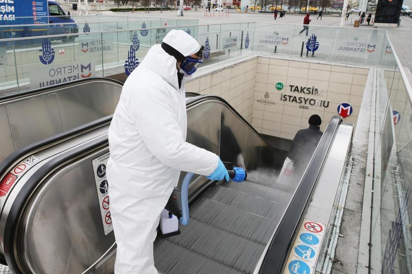 İstanbul Taksim metro istasyonunun girişlerinden birinde görveliler dezenfekte işlemi yaparken.