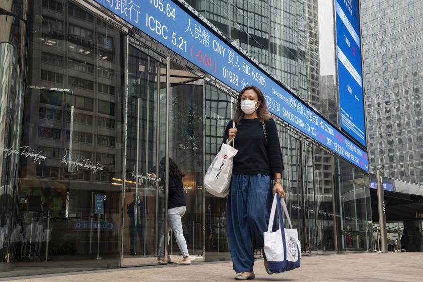 Maske takan ve elinde market torbalarıyla yürüyen bir kadın