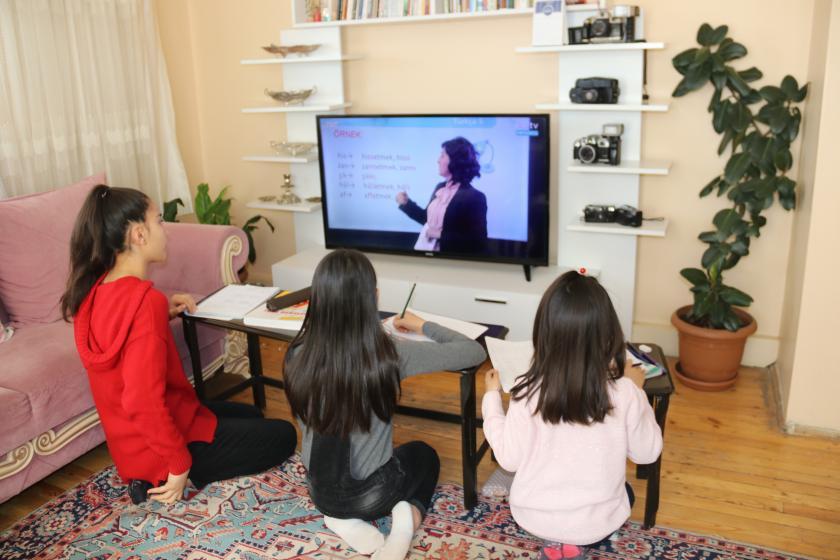 televizyonun önünde oturan üç çocuk