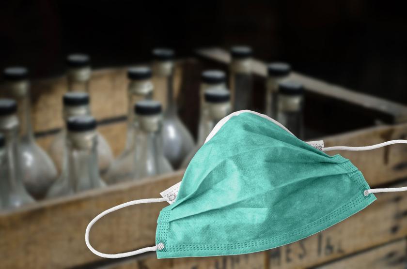 Arkada tahta sandığın içinde çok sayıda şişe ve önde yeşil bir maskeden oluşan kolaj.