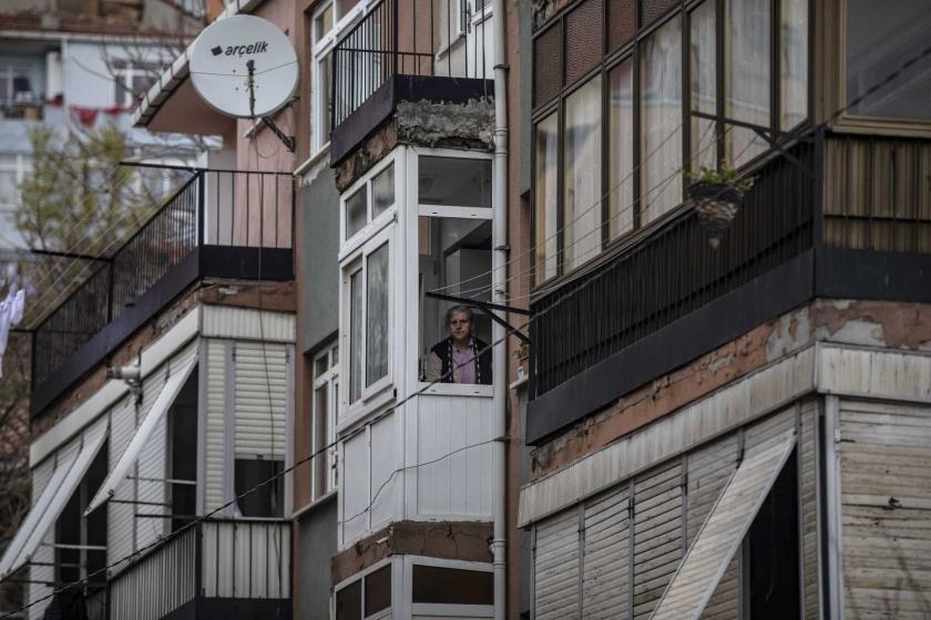 İstanbul'da koronavirüs (Kovid-19) salgını dolayısıyla alınan önlemler sonrası evinin camından dışarıya bakan bir yaşlı kadın.