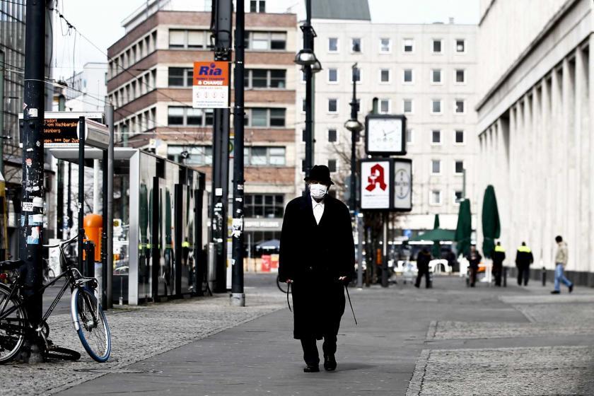 Almanya'da koronavirüs (Kovid-19) salgını dolayısıyla alınan önlemler sonrası boş bir caddede yüzünde maske ile yürüyen bir erkek.