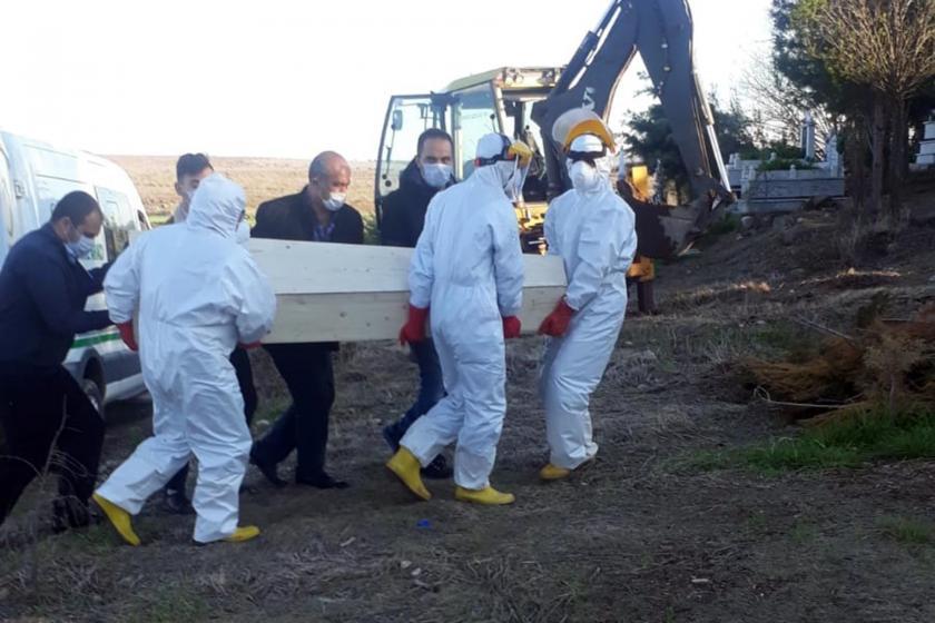 Koruma kıyafetleri ile cenaze taşıyanlar