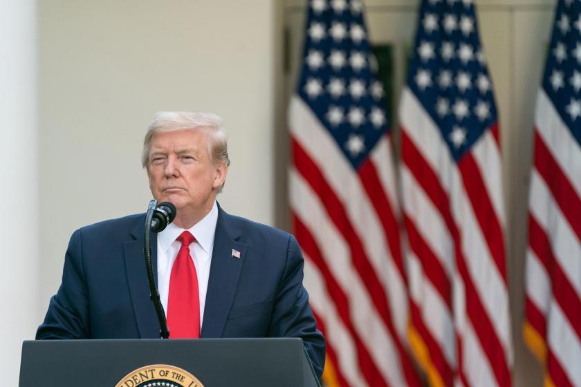 ABD Başkanı Donald Trump ABD bayrakları önünde konuşuyor.