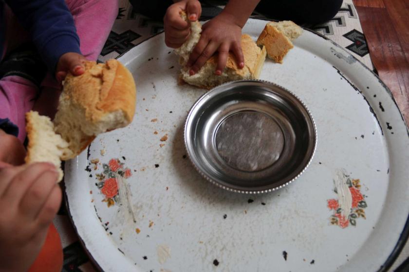 Tepsideki ekmekleri tutan çocuk elleri.