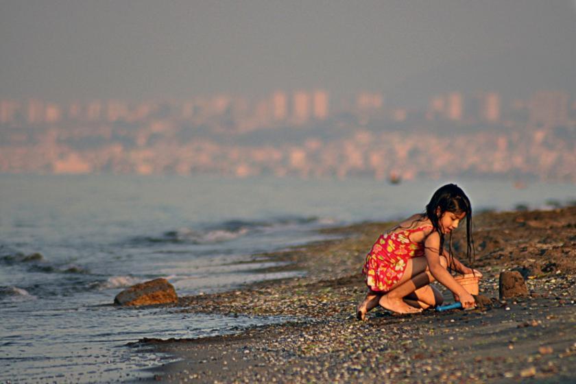 Sahilde bir kız çocuğu kumla oynuyor