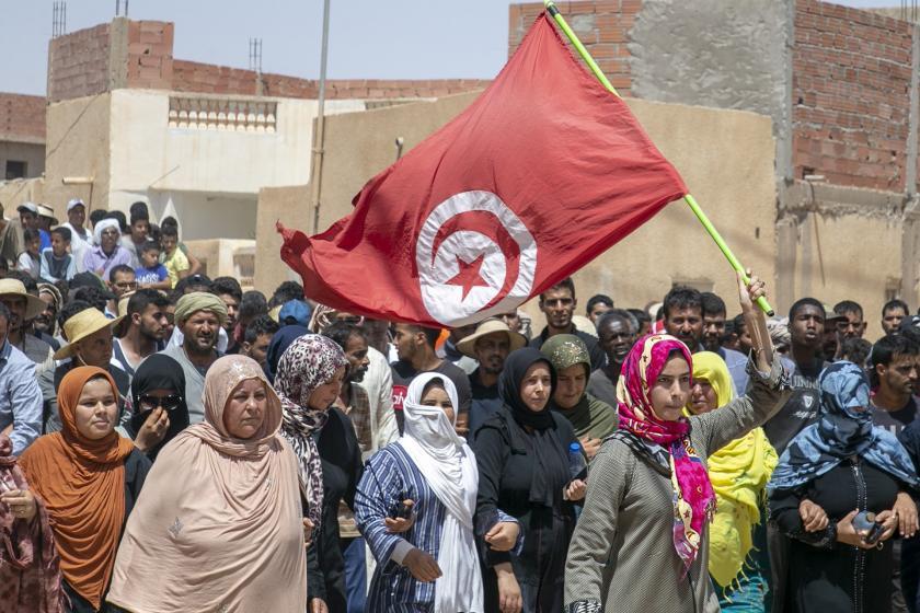 Elindeki Tunus bayrağını yukarı kaldıran bir kadın (sağda)