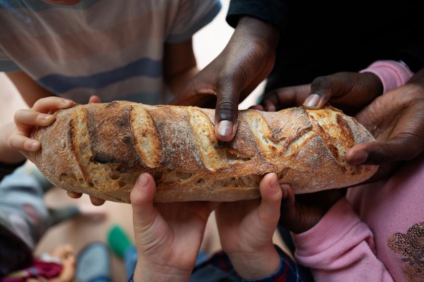 Farklı ırklardan çocuklar tek bir ekmeği tutuyor.